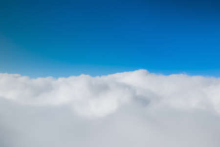 Photograph taken on top of cloud with blue sky.