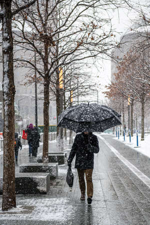 A man with umbrella walks trgough snowy weather in lower Manhattan.
