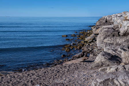 A rock jetty against the blue sky and calm Bering Sea in Nome Alaska.