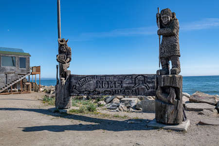 The wooden carved monument depicting a gold panner and native Alaskan on the shore of the Bering Sea in Nome Alaska.