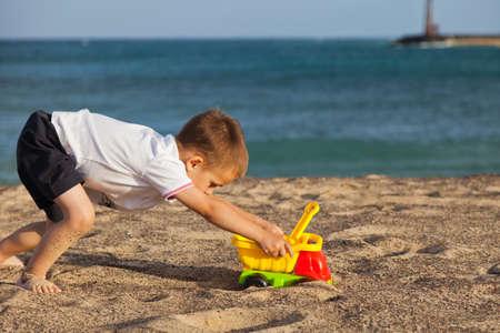 ni�o empujando: Ni�o empujando su coche de juguete en la playa de Lanzarote