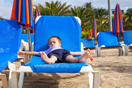 sunbed: A child lying flat on a sunbed