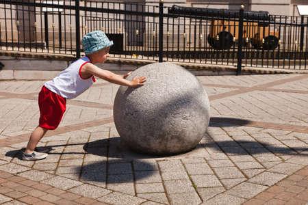 ni�o empujando: Ni�o empujando una gran bola pesada Foto de archivo