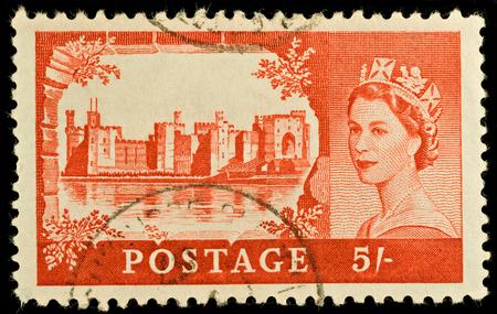 BRITAIN - CIRCA 1967: An old British five shilling stamp showing Caernarvon Castle and portrait of Queen Elizabeth II, circa 1967