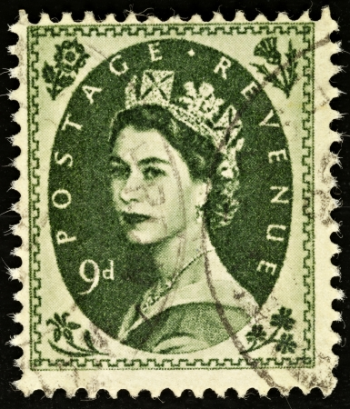 UNITED KINGDOM - CIRCA 1952 to 1965: An English Nine Pence Green used Postage Stamp showing Portrait of Queen Elizabeth 2nd, circa 1952 to 1965