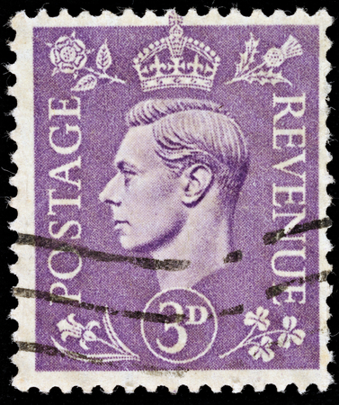 UNITED KINGDOM - 1937 - 1947: An English Three Pence Violet Used Postage Stamp showing Portrait of King George VI, 1937 - 1947