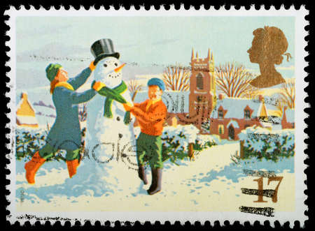 UNITED KINGDOM - CIRCA 1990  A British Used Christmas Postage Stamp showing Children Building a Snowman, circa 1990
