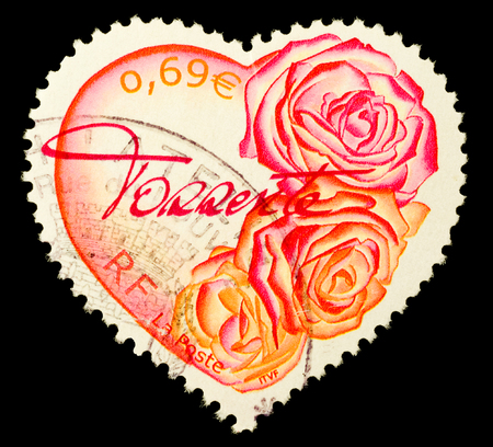 FRANCE - CIRCA 2003  A Heart Shaped Stamp showing pink and red roses isolated on black background, circa 2003