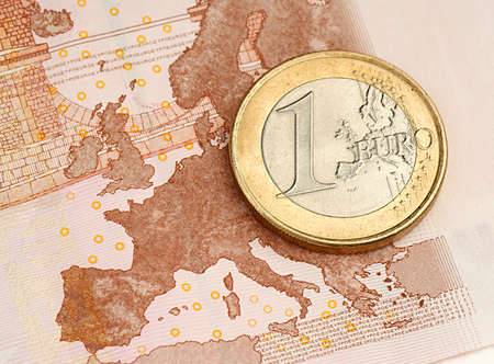 One Euro Coin on Euro Banknote showing Map of Europe photo