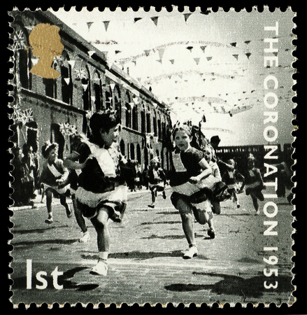 street party: UNITED KINGDOM - CIRCA 2003: British Postage Stamp celebrating the 50th Anniversary of the Coronation in 1953 of Queen Elizabeth 2nd, showing a street party, circa 2003