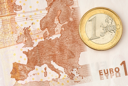 One Euro Coin on Euro Banknote showing Map of Europe Stock Photo