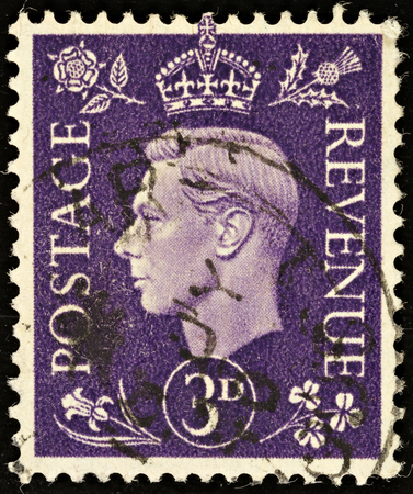 UNITED KINGDOM - CIRCA 1937 to 1947: An English Three Pence Violet Used Postage Stamp showing Portrait of King George VI, circa 1937 to 1947