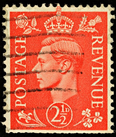 two and a half: UNITED KINGDOM - CIRCA 1950 to 1952: An English Two and a Half Pence Red Used Postage Stamp showing Portrait of King George VI, circa 1950 to 1952