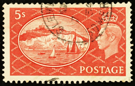 shilling: UNITED KINGDOM - CIRCA 1951: An English Five Shilling Red Used Postage Stamp showing Portrait of King George VI and the White Cliffs of Dover, circa 1951