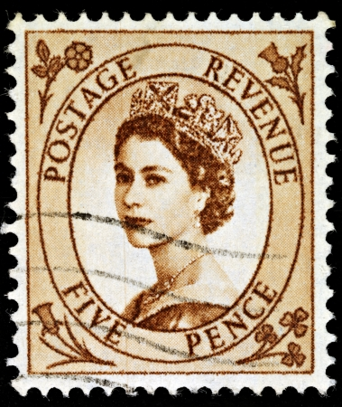 pence: UNITED KINGDOM - CIRCA 1952 to 1965: An English Five Pence Brown Used Postage Stamp showing Portrait of Queen Elizabeth 2nd, circa 1952 to 1965