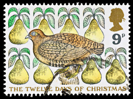 UNITED KINGDOM - CIRCA 1977: Used Christmas Postage Stamp depicting the Carol The Twelve Days of Christmas showing a Partridge in a Pear Tree, circa 1977