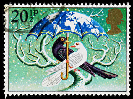 UNITED KINGDOM - CIRCA 1983: A British Used Christmas Postage Stamp depicting World at Peace showing a Dove and Blackbird, circa 1983 Editorial
