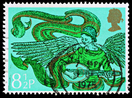 franked: UNITED KINGDOM - CIRCA 1975: A British Used Postage Stamp showing an Angel with Mandolin, circa 1975  Editorial
