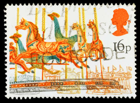 fairs: UNITED KINGDOM - CIRCA 1983: A used postage stamp printed in Britain celebrating British Fairs showing a Carousel Merry Go Round Amusement Ride