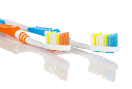Closeup of Pair of Toothbrushes On White Background with Reflection photo