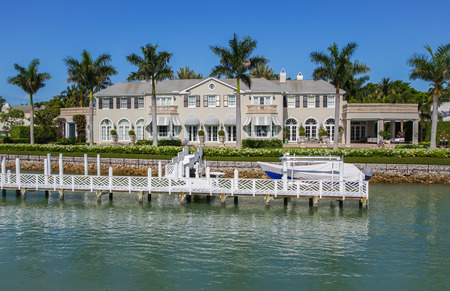 NAPLES, FLORIDA USA - May 8 2013: Luxury waterside mansion with jetty boat dock in the bayside area of Naples. Naples is one of the wealthiest cities in the United States