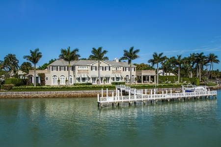 Naples, Florida USA - 8 mei 2013: Luxe waterkant herenhuis met aanlegsteiger boot dok in de Bayside gebied van Napels. Napels is een van de rijkste steden in de Verenigde Staten