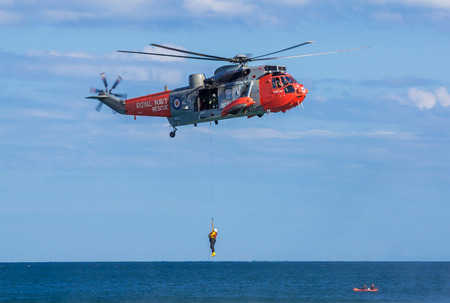 DAWLISH, UNITED KINGDOM - AUGUST 23, 2014: Royal Navy Sea King Search and Rescue Helicopter Demonstrating Winch Rescue at the Dawlish Airshow