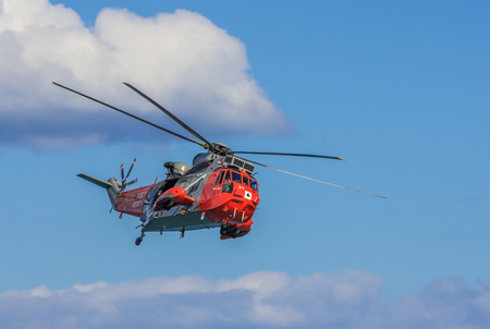 DAWLISH, UNITED KINGDOM - AUGUST 23, 2014: Royal Navy Sea King Search and Rescue Helicopter Flying at the Dawlish Airshow