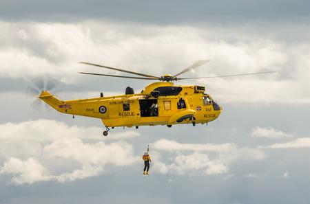 king: DAWLISH, Reino Unido - 23 de agosto 2014: Royal Navy Sea Rey de B�squeda y Rescate Vuelo del helic�ptero en el Dawlish Airshow Demostrando Winch Rescate