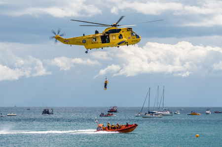 inshore: DAWLISH, UNITED KINGDOM - AUGUST 23, 2014: Royal Navy Sea King Search and Rescue Helicopter Flying at the Dawlish Airshow