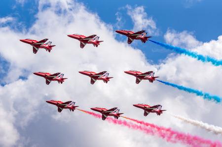 high performance: DAWLISH, UNITED KINGDOM - AUGUST 23 2014: The Royal Air Force Red Arrows aerobatics display team flying at the Dawlish Airshow Editorial