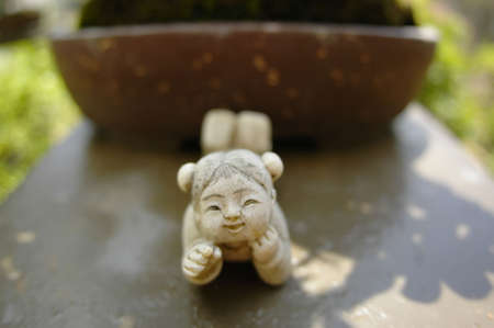Stone figurine in front of bonsai tree Stock Photo