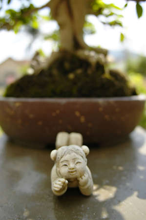 Stone figurine in front of bonsai tree Stock Photo