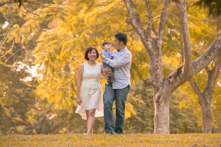 Asian young family having fun outdoors in autumn
