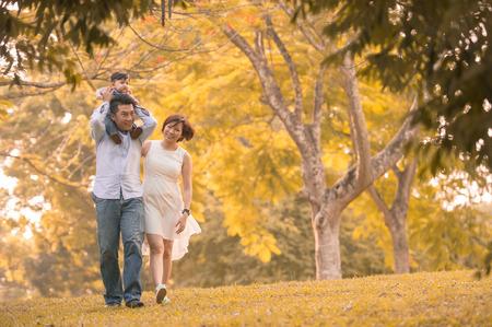 Asian young family having fun outdoors in autumn photo