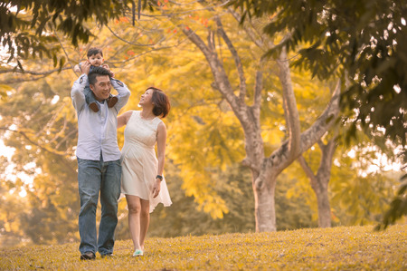 Asian young family having fun outdoors in autumn photo