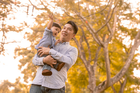Asian father and son having fun outdoors