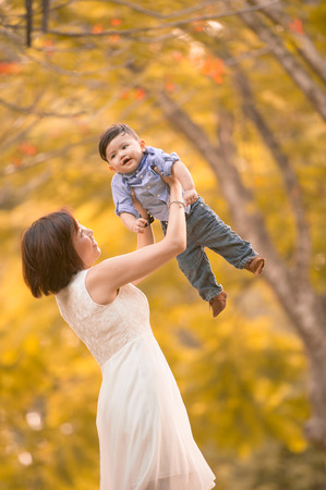 Asian mother and son having fun outdoors  Stock Photo