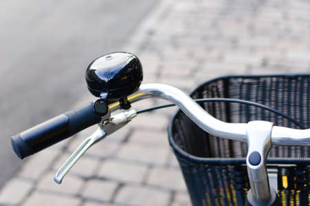 Black shiny bicycle bell and front basket photo
