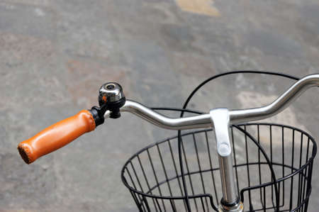 Yellow leather grip, black bicycle bell and front basket photo