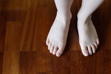 children s feet: Baby feet on the parquet Stock Photo