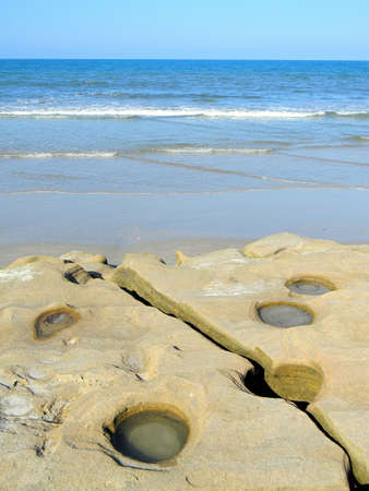 coquina: Shattered coquina rocks along the blue ocean waters of a Florida beach. Stock Photo
