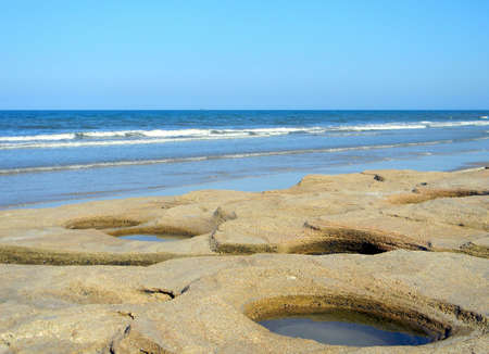 Naturally carved holes in coquina rocks over looking the ocean.
