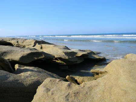 coquina: Marea alta empuja en una abertura en una playa de coquina rocosas.