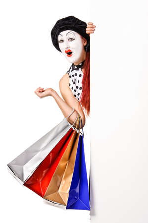 Pretty mime woman holding blank billboard and shopping bags  Isolated on white background  photo
