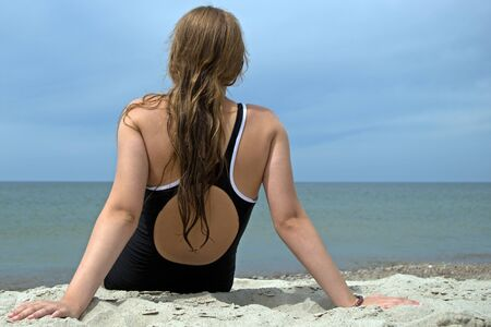 A girl in a black one-piece swimsuit, sitting on a sandy beach with her back to the viewer, looking into the distance Stockfoto