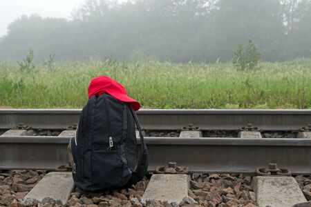Black backpack with red cap on it next to railway in the background of meadow, trees and foggy sky