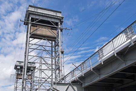 Construction white gray metal two-tier draw bridge over the river, bottom view of the second tier with railway tracks and two pillars in the form of towers against a cloudy blue sky