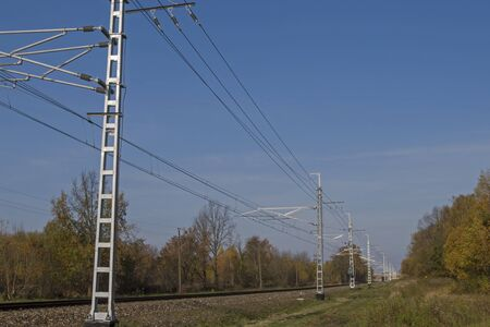 Railway embankment with railroad tracks stretching into distance and perspective above them a power line for the movement of an electric train against a blue sky and trees with green foliage on sides