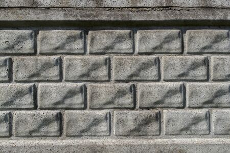 A fragment of gray concrete relief wall or fence imitating several rows of rectangular bricks laid horizontally. Abstract architectural or industrial background